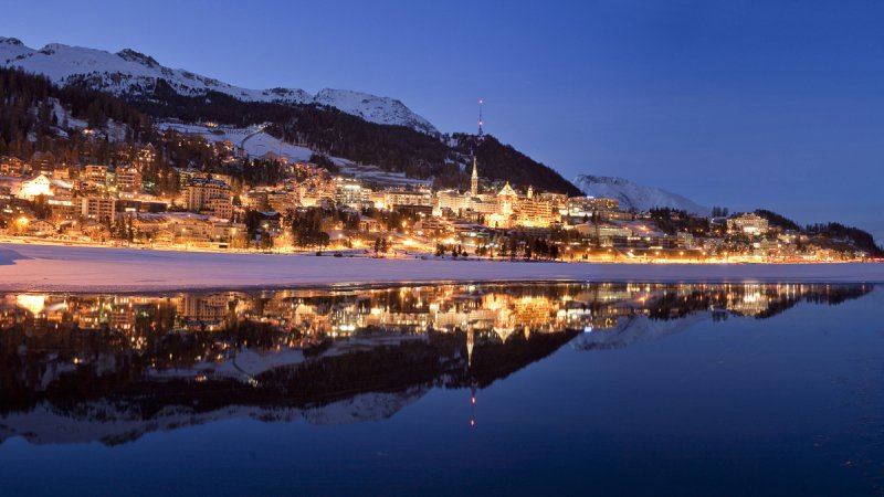 St. Moritz at dusk. View from the bank of Lake Moritz of the lit-up resort of St. Moritz with Badrutt's Palace Hotel.